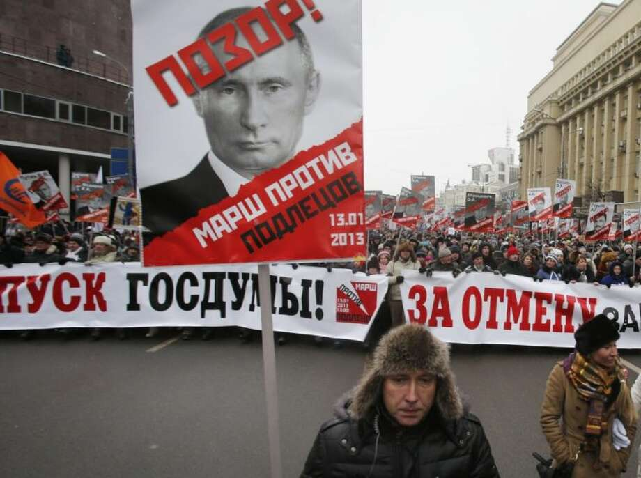 "People carry posters of Russian President Vladimir Putin with the words reading ""March Against the Scum and Shame"" during a protest rally in Moscow, Russia, Sunday, Jan. 13, 2013, with the banner reading ""Dissolution of the State Duma"". Photo: Misha Japaridze / AP2013"