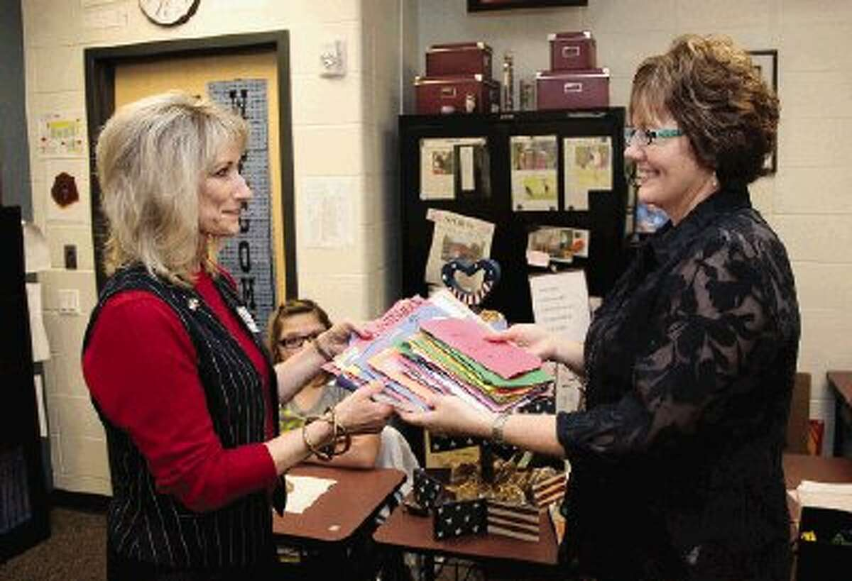 Conroe Cookie Convoy founder Marlene Summers, left, accepts handwritten cards and notes of encouragement that will be sent to military personnel overseas from Montgomery Middle School teacher Chris Corson.