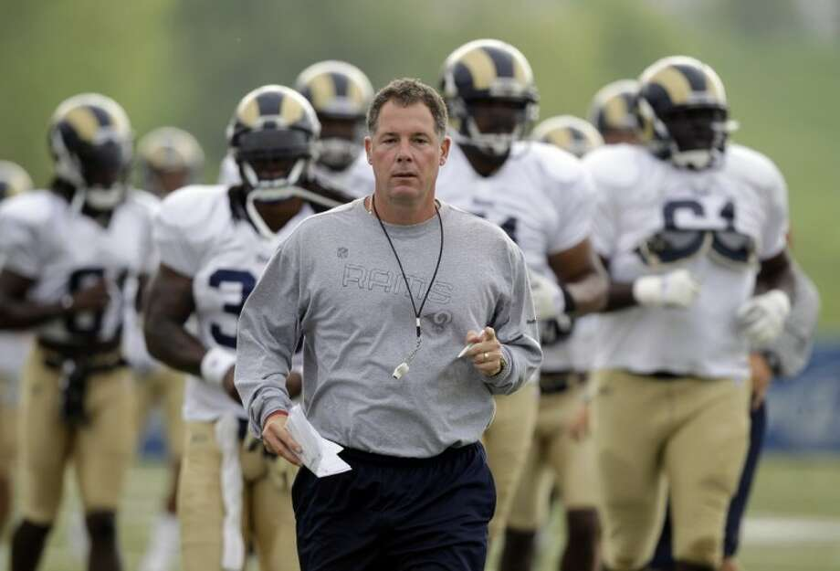 New Cleveland Browns head coach and former St. Louis Rams offensive coordinator Pat Shurmur jogs with members of the Rams during training camp at the team's training facility in St. Louis on Aug. 5.