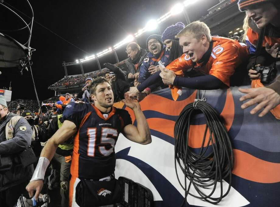 Denver Broncos quarterback Tim Tebow celebrates with fans after the Broncos beat the Pittsburgh Steelers 29-23 in overtime Sunday in Denver. Photo: Jack Dempsey