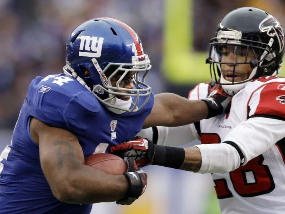 New York Giants running back Ahmad Bradshaw stiff arms Atlanta Falcons free safety Thomas DeCoud during the second half Sunday in East Rutherford, N.J. Photo: Peter Morgan