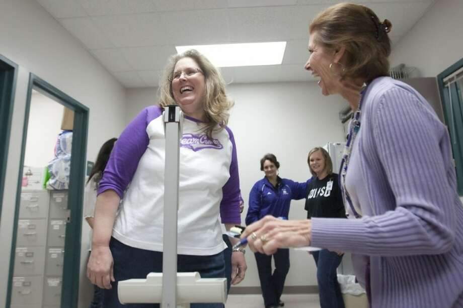 Willis High School Nurse Dorothy Wilkinson weighs Sandy Coleman for the Biggest Loser competition Friday at Willis High School. The money raised will benefit a student battling Hodgkin's Lymphoma. Photo: Karl Anderson