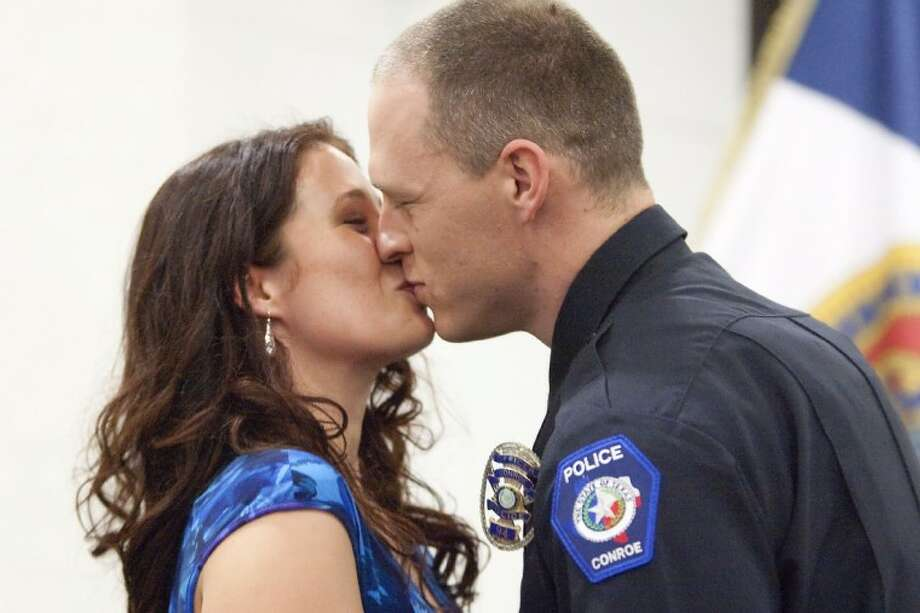Jennifer Atherton kisses her husband Justin after pinning on his badge during the Conroe Police Academy graduation ceremony Thursday at the Conroe Tower. See more photos online at www.yourconroenews.com/photos. Photo: Staff Photo By Karl Anderson