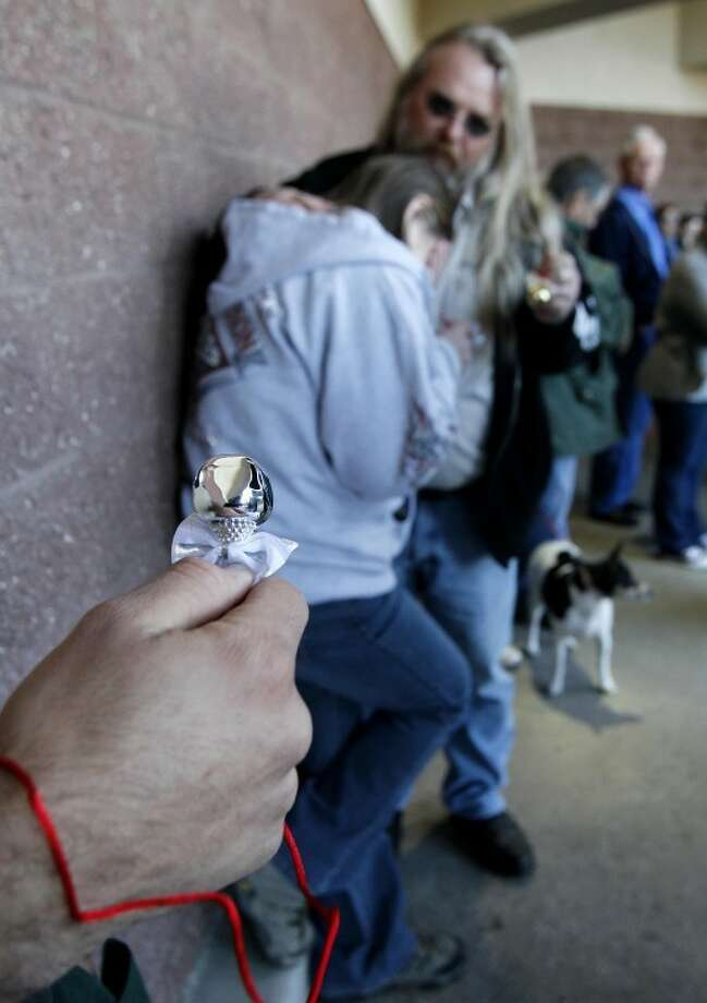 Edgar Clement heads a line of people as they ring bells outside the Safeway grocery store, Sunday, Jan. 8, 2012, in Tucson, Ariz., where U.S. Rep. Gabrielle Giffords, D-Ariz., was shot one year ago during a shooting spree that left 6 dead and 13 wounded, including Giffords. (AP Photo/Matt York) Photo: Matt York