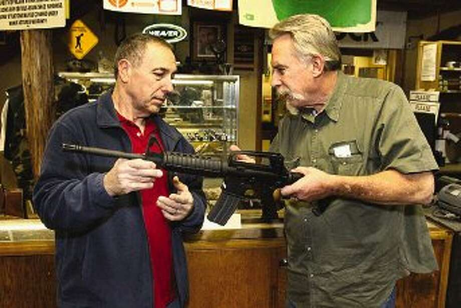 Conroe Shooting Center & Gun Emporium Manager Mike Scambray, left, and gunsmith Mike Morrison examine an AR-15 rifle with a 20-round clip, the type of weapon and high-capacity ammunition magazine under fire by gun control advocates.