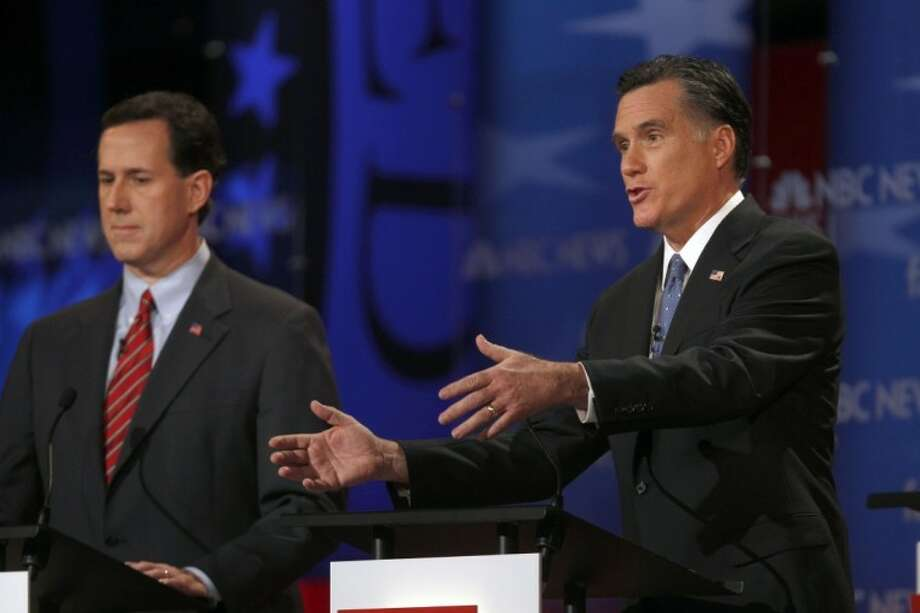 Former Massachusetts Gov. Mitt Romney, right, answers a question and former Pennsylvania Sen. Rick Santorum listens during a Republican presidential candidate debate at the Capitol Center for the Arts in Concord, N.H., Sunday, Jan. 8, 2012. Photo: Charles Krupa