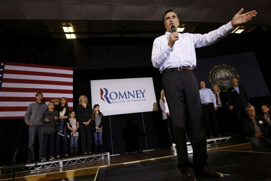 With his family behind him, Republican presidential candidate, former Massachusetts Gov. Mitt Romney, campaigns at McKelvie Intermediate School in Bedford, N.H., Monday, Jan. 9, 2012. (AP Photo/Charles Dharapak) Photo: AP Photo