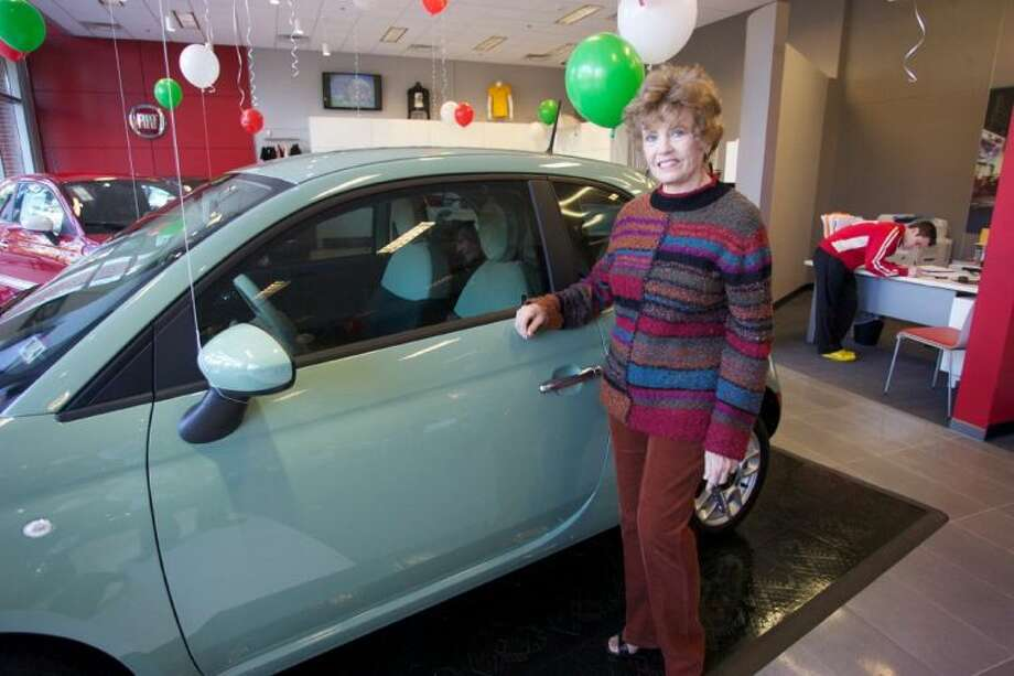 "Ann Taylor, of Willis, stands next to her new Fiat 500 which she won in Fiat's ""Spring Past Winter"" promotion. Taylor took delivery of the Fiat at Northside Fiat located at 1501 Lake Robbins Drive in The Woodlands. Photo: Staff Photo By Eric Swist"
