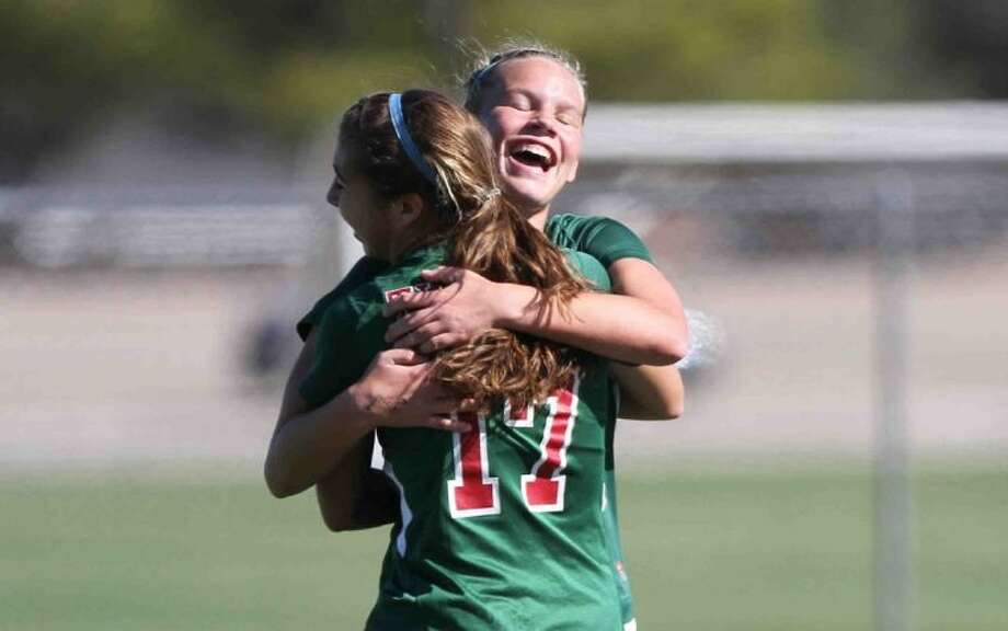 The Woodlands midfielder Grace Piper hugs Carmen Webster (17) after her goal in the second half of Friday's match against Clements in the I-10 Shootout at Cinco Ranch High School. The Lady Highlanders won 2-1. To see more photos from the game, visit HCNpics.com. Photo: Jason Fochtman