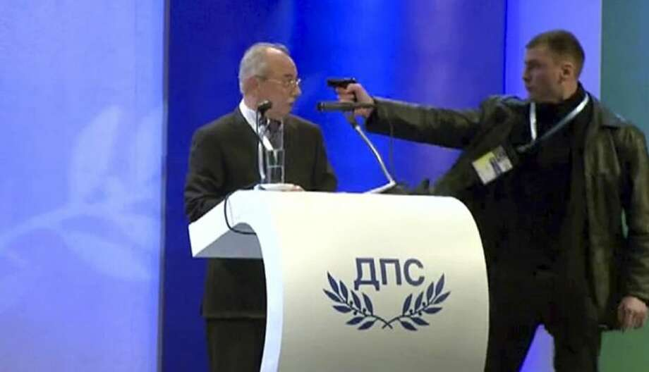 Image grab from video shows a man identified as Oktai Enimehmedov, 25, as he points a weapon at Ahmed Dogan, left, leader of the Movement for Rights and Freedoms, during his speech at his party's congress in Sofia, on Saturday. Dogan struck the man before other delegates wrestled the assailant to the ground, and no shots were fired. Police took the man away. Photo: Btv News