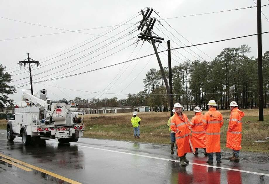 Entergy Texas repair crews assess damage caused when the support wires for a distribution pole pulled loose near the Conroe Bulk substation on South Frazier Street due to heavy rains Monday. Power to about 1,500 people, including Conroe Regional Medical Center and businesses around it, was lost for a portion of Monday afternoon. Photo: Staff Photo By Brad Meyer