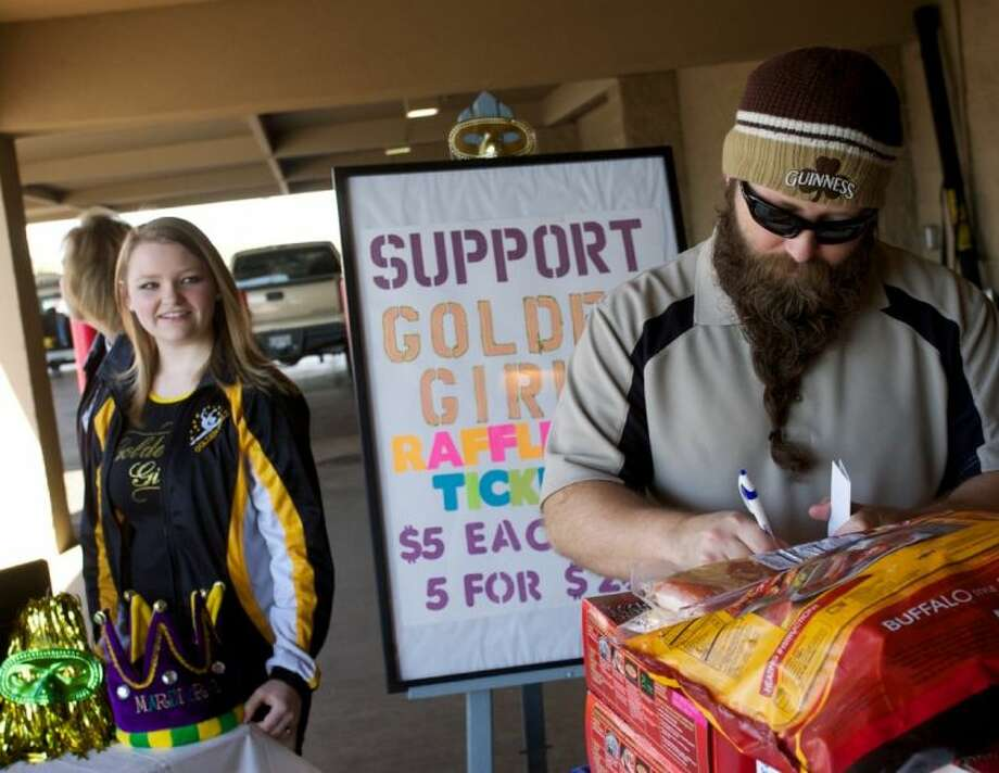 A shopper takes a moment to buy raffle tickets to support the Conroe High School Golden Girls as members of the team stood outside the Sam's Club in Conroe Saturday morning. Team members were selling raffle tickets and tickets to their annual pancake fundraiser. Photo: Staff Photo By Eric Swist