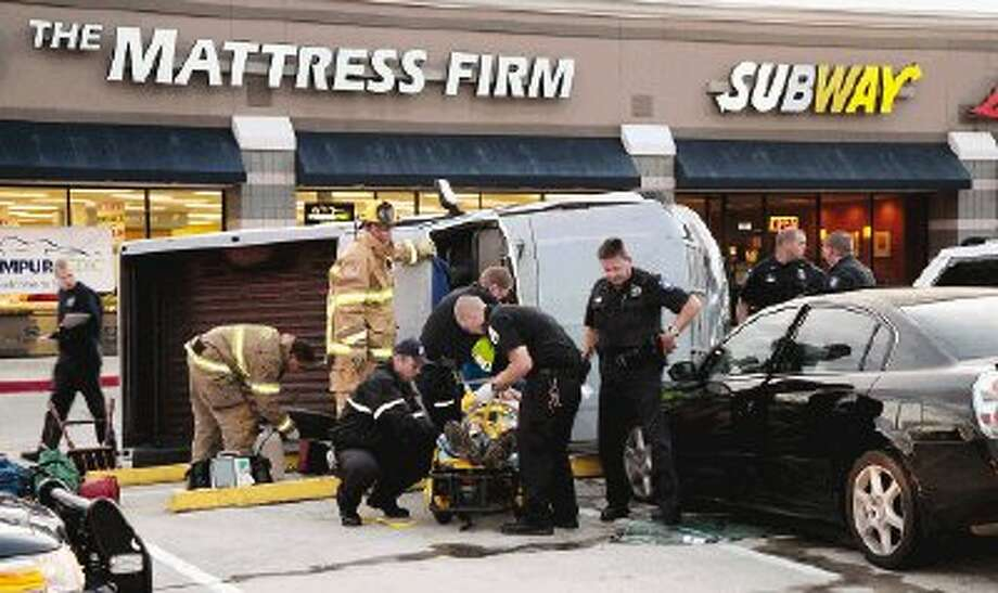 Emergency medical workers tend to the driver of a pickup truck that damaged three vehicles in an alleged hit-and-run accident in the Home Depot parking lot in Conroe early Tuesday evening. The driver was transported to Conroe Regional Medical Hospital.