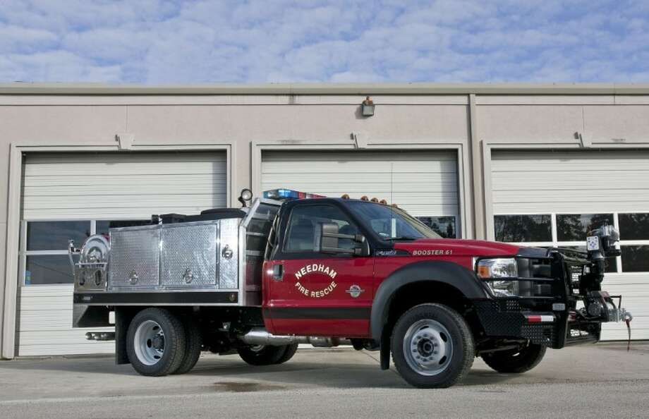 "The newest booster truck, Booster 61, for the Needham Fire Department is seen outside the station. The truck, a Ford F-450, was purchased with the help of a grant from the Texas Forest Service. The truck features a unique ""bumper turret,"" which has an automatic nozzle and can be controlled from inside the cab."