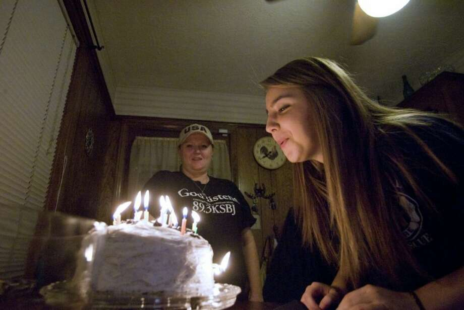 Turkish exchange student Rengin Bakal blows out the candles on her birthday cake Wednesday as host mother Missy Borne looks on at the family's home in Conroe. Photo: Staff Photo By Eric S. Swist