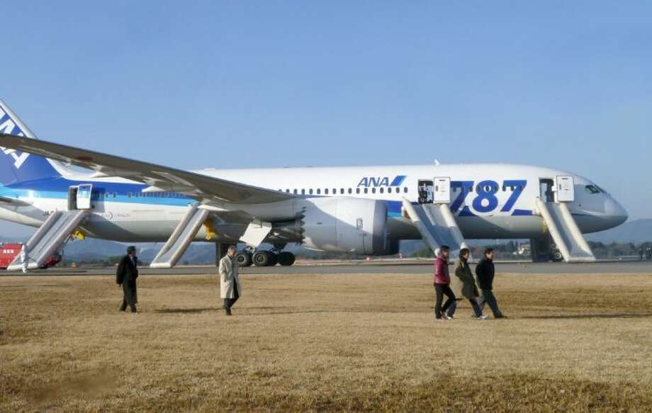 In this photo taken by a passenger and distributed by Japan's Kyodo News, passengers leave an All Nippon Airways Boeing 787 after it made an emergency landing at Takamatsu airport in Takamatsu, Kagawa Prefecture, western Japan, Wednesday.