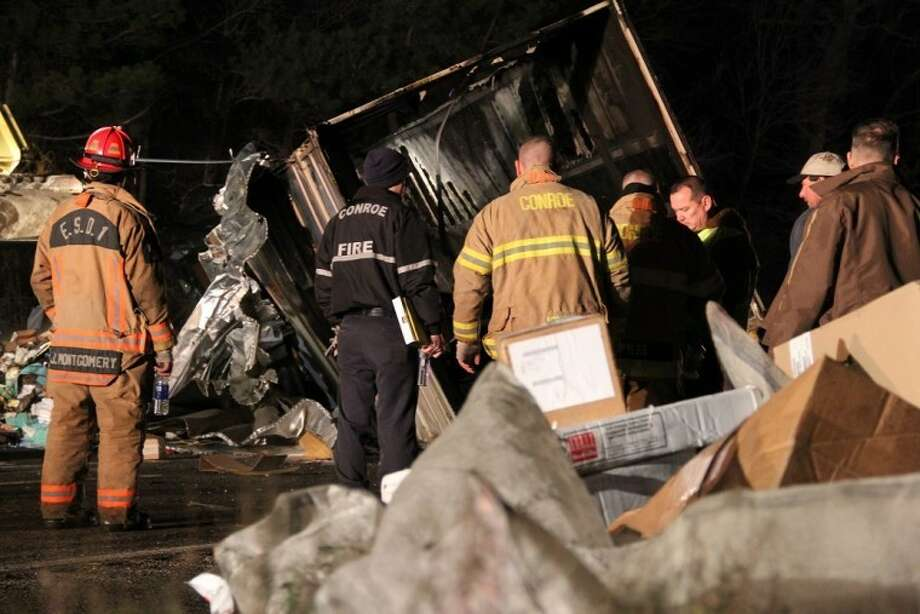 Conroe police and firefighters work to clear the scene of a UPS truck that struck a guardrail on Interstate 45 near FM 830 late Wednesday night. Photo: Staff Photo By James Ridgway Jr.