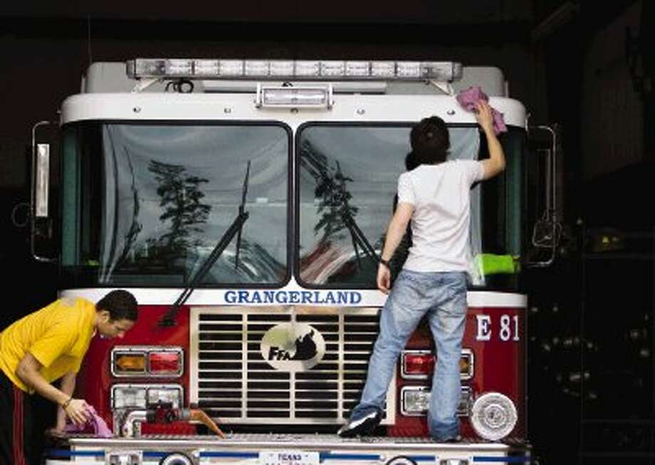 Junior firefighters Cory Heggins, 17, left, and Bryan Pond, 18, dry off Engine 81 at the Caney Creek Volunteer Fire Department's Station 81 in Grangerland Tuesday. Photo: Staff Photo By Eric S. Swist