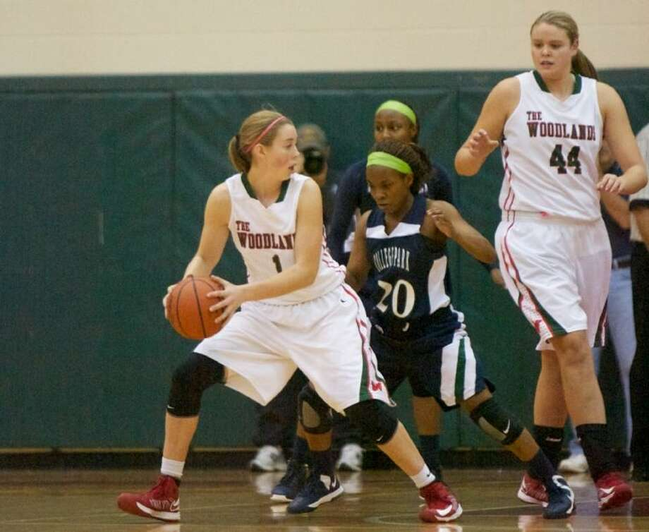 The Woodlands' Nicole Lademarco looks for an open teammate as she comes under pressure from College Park's Amaris Hollis during Tuesday night's District 14-5A game at The Woodlands High School. Photo: Staff Photo By Eric Swist