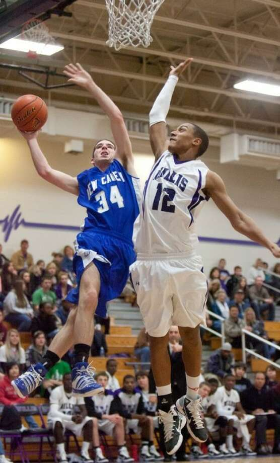 New Caney's Reed Thomas drives to the basket against Willis' Quan West during Friday night's district game at Willis High School.