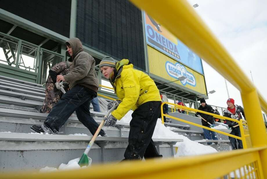 Jackson Ranck, center, of Pulaski, Wis., shovels snow with hundreds of others in an effort to clear snow from the upper level bleachers inside Lambeau Field on Friday ahead of Sunday's NFL divisional playoff football game between the New York Giants and Green Bay Packers. Photo: Corey Wilson