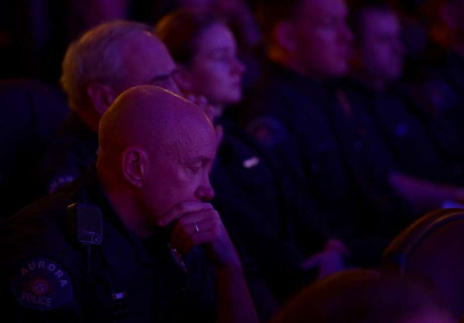 Aurora Police Officer Mike Hawkins, an 18-year veteran and first responder to the shooting, sits with other Aurora Police officers during the reopening and remembrance ceremony at the Century Aurora cinema, formerly the Century 16, Thursday in Aurora, Colo. The cinema is where 12 people were killed and dozens injured in a shooting rampage last July. Photo: RJ Sangosti