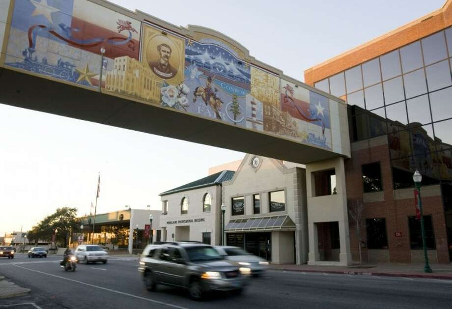 """Cars pass under the 70-foot mural """"The Montgomery County Walkway Through Time"""" on Texas 105 East in downtown Conroe. The artist behind the work, Mark Clapham, died in his Conroe home Thursday at the age of 63. Photo: Staff Photo By Eric S. Swist"""