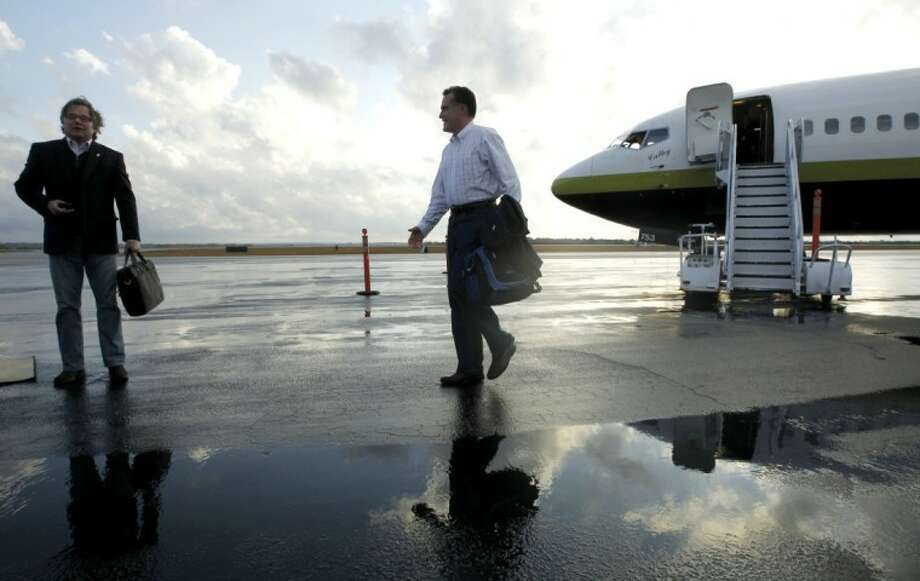 Republican presidential candidate, former Massachusetts Gov. Mitt Romney, walks towards adviser Eric Fehrnstrom, left, as they stepped off his campaign charter plane in Columbia, S.C., Wednesday, Jan. 11, 2012, the day after winning the New Hampshire primary election. Photo: Charles Dharapak