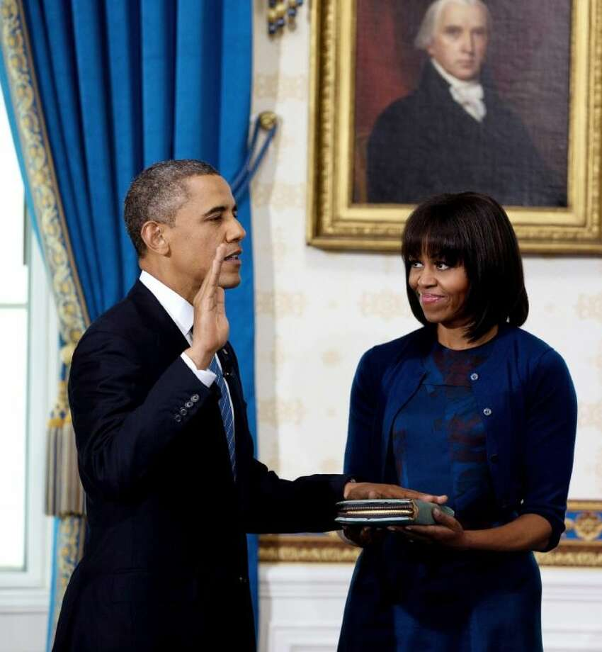 President Barack Obama is officially sworn-in by Chief Justice John Roberts, not pictured, in the Blue Room of the White House Sunday in Washington, as first lady Michelle Obama holds the Robinson Family Bible. Photo: Doug Mills
