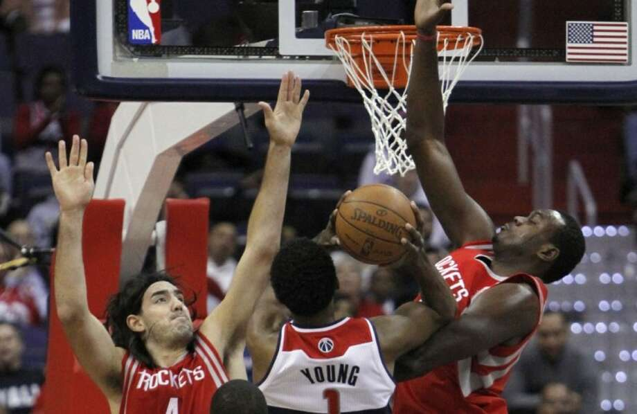 Houston Rockets forward Luis Scola, guard Kyle Lowry, and center Samuel Dalembert, block Washington Wizards guard Nick Young, as he takes a shot during the first quarterat the Verizon Center in Washington, on Monday. Photo: Jacquelyn Martin