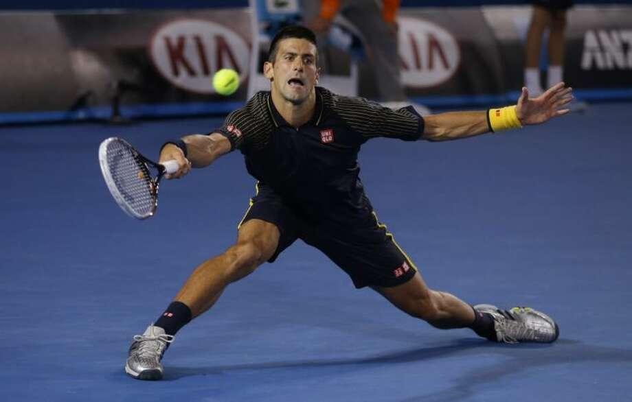 Serbia's Novak Djokovic hits a forehand return to Sanislas Wawrinka. Djokovic needed five hours and as many sets to advance in the Australian Open. Photo: Dita Alangkara