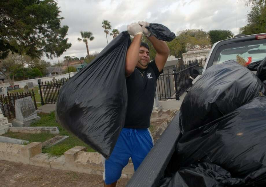 Criminal Justice major, Joseph Martinez, carries plastic bags of debris to a pickup to be hauled off from the the Old Brownsville City Cemetery in Brownsville Monday. Students from the University of Texas at Brownsville volunteered their time on Martin Luther King Day and spent their morning cleaning. Photo: Brad Doherty