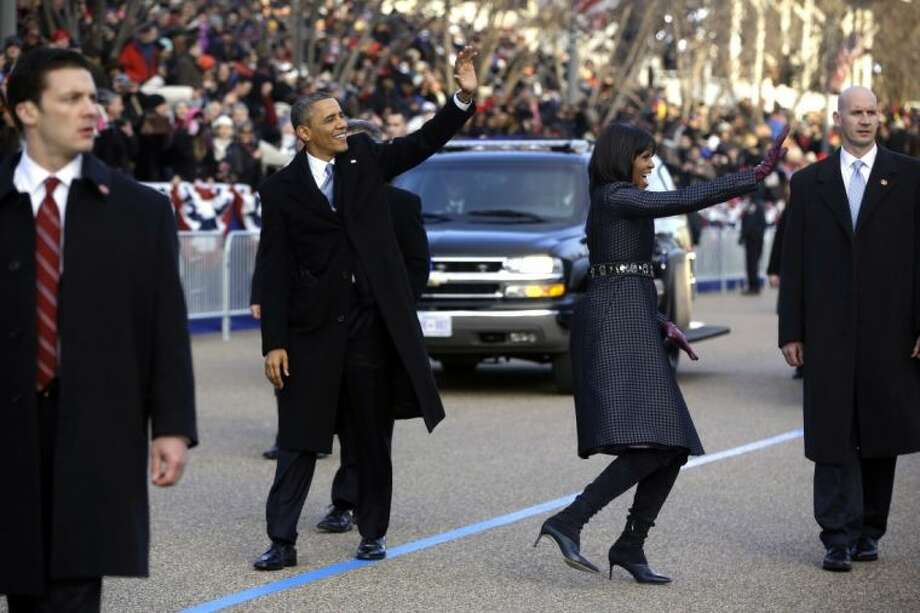 President Barack Obama and first lady Michelle Obama wave as they walk on Pennsylvania Avenue in Washington, Monday,Jan. 21, 2013, in the inaugural parade during the 57th Presidential Inauguration. Photo: Charles Dharapak
