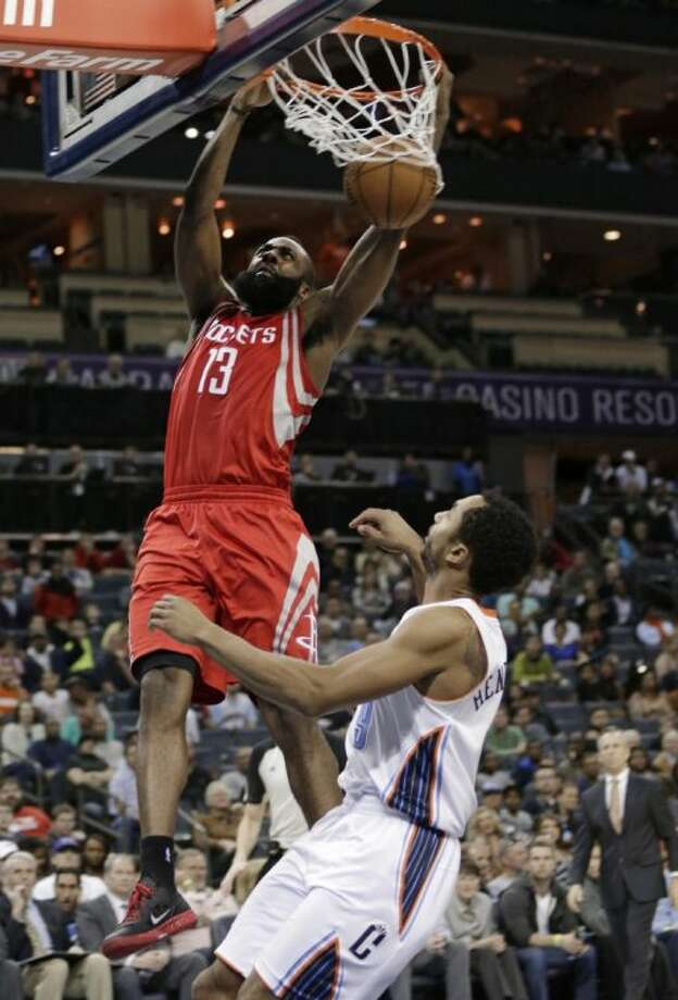The Rockets' James Harden dunks over the Bobcats' Gerald Henderson. The Rockets won 100-94. Photo: Chuck Burton