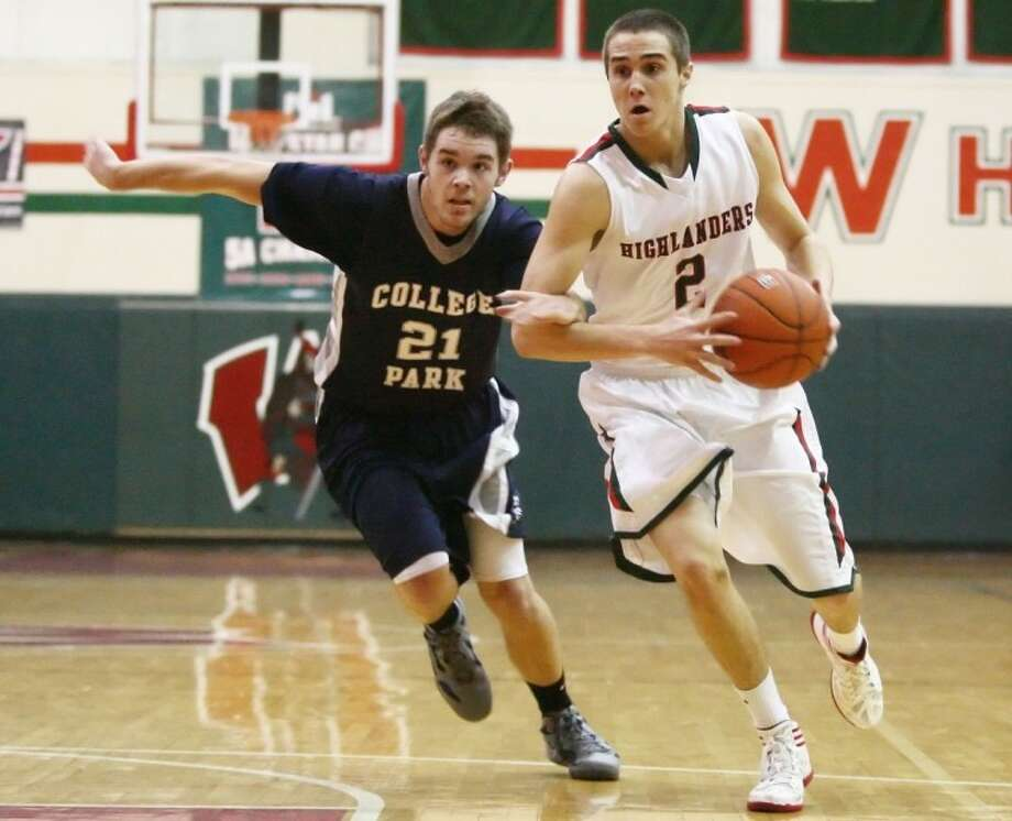 The Woodlands' Garret Colonna makes his way to the basket while College Park's Justin Mauck chases in the two teams' meeting at The Woodlands High School. Photo: Staff Photo By Karl Anderson