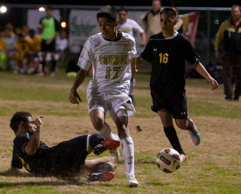 An Eisenhower defender tackles Conroe's Jose Luis Sanchez during Tuesday night's match at Conroe High School.