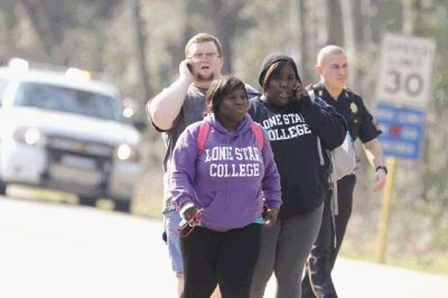 Women wearing Lone Star College sweatshirts and a man walk with a police officer near the North Harris campus of Lone Star College in Houston after a shooting that wounded three people and sent students fleeing for safety. See video interview online at YourConroeNews.com. / Jason Fochtman