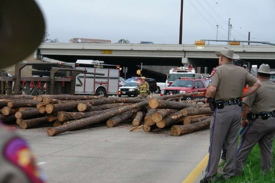 Texas Department of Public Safety troopers look out on the scene of an overturned lumber truck early Thursday morning. The accident shut down Texas 242 East for a few hours.