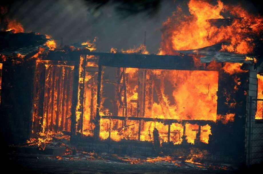 A house burns just south of the Old 395 Gas Station Thursday in Washoe Valley, Nev. Winds gusting up to 82 mph pushed a fast-moving brush fire south of Reno out of control on Thursday as it burned several homes, threatened dozens more and forced more than 4,000 people to evacuate their neighborhoods. Photo: Liz Margerum