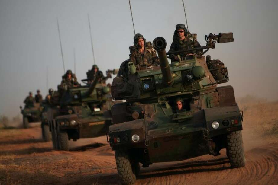 French soldiers patrol in armored vehicles, in the outskirts of Sevare, Mali, some 620 kms (385 miles) north of Bamako, Wednesday, Jan. 23, 2013. The U.S. airlift of French forces to Mali to fight Islamic extremists is expected to go on for another two weeks, Pentagon officials said, as hundreds of African troops from Nigeria, Togo, Burkina Faso and Senegal are now joining the French-led intervention. Photo: Thibault Camus