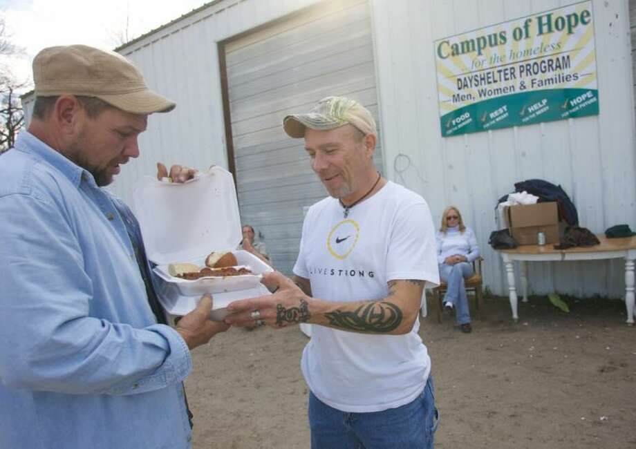 John Anderson, the head cook at Campus of Hope, chats with a resident who picked up a package of food from the center's kitchen. Without use of stove top burners, Anderson prepares most of the meals in an oven. Photo: Staff Photo By Eric Swist