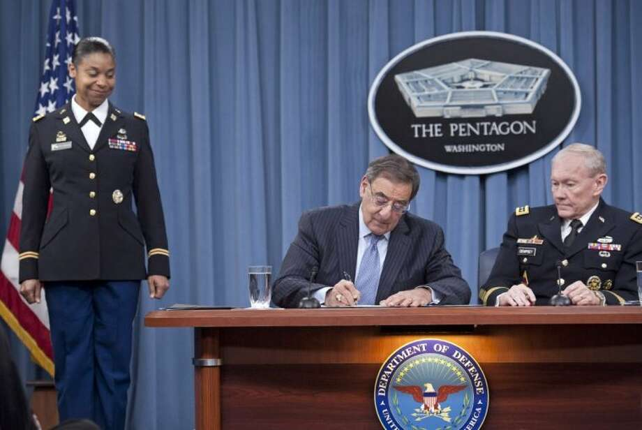 Defense Secretary Leon Panetta, flanked by Joint Chiefs Chairman Gen. Martin Dempsey, right, and Army Lt. Col. Tamatha Patterson, of Huntingdon, Tenn., signs a memorandum ending the 1994 ban on women serving in combat roles in the military, Thursday, Jan. 24, 2013, at the Pentagon. Photo: Cliff Owen