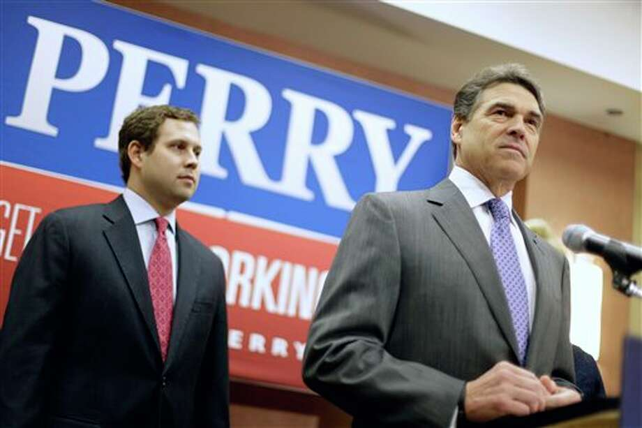Republican presidential candidate, Texas Gov. Rick Perry pauses during a news conference in North Charleston, S.C., Thursday, Jan. 19, 2012, where he announced he is suspending his campaign and endorsing Newt Gingrich. His son Griffin is at left. (AP Photo/David Goldman) Photo: David Goldman / AP2012