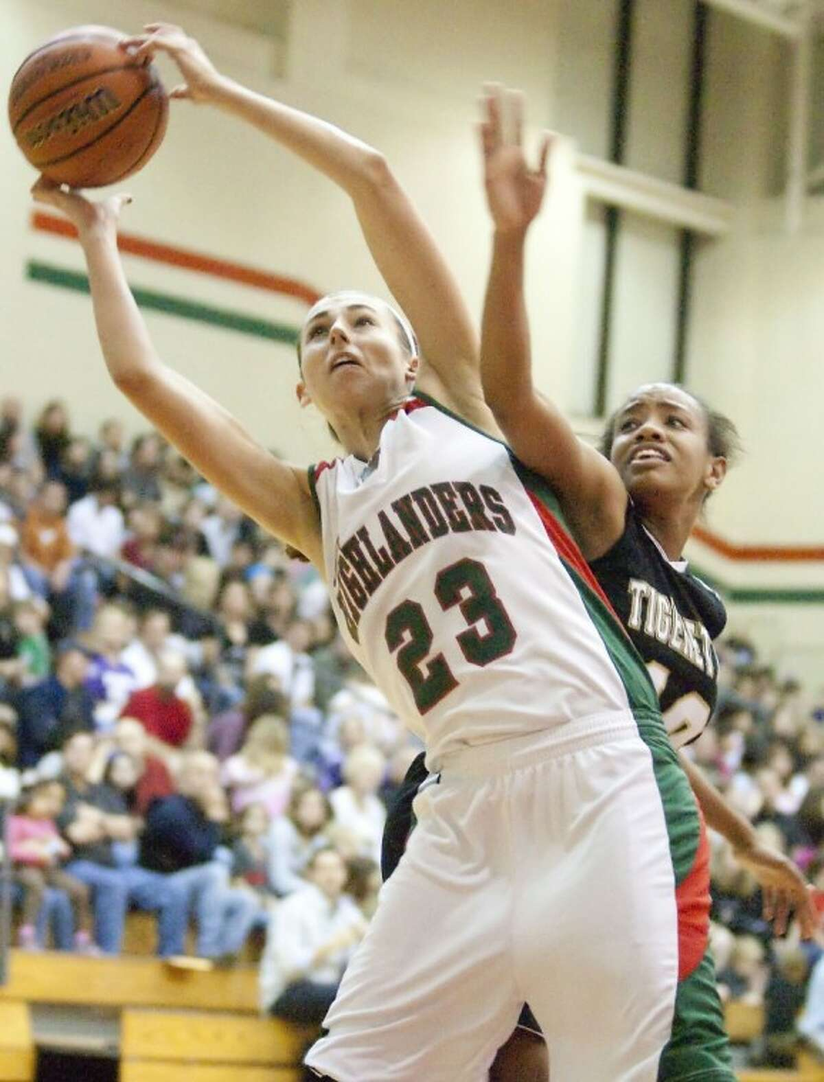 The Woodlands' Anna Strickland hauls in a rebound during a game against Conroe. Strickland was named The Courier's 2011-2012 All-Montgomery County Player of the Year.