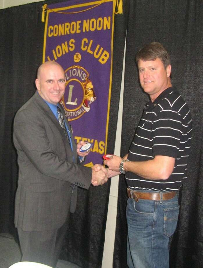 Conroe Noon Lions Club President Philip Dupuis exchanges official with the blue permanent member badge with new member Dennis Gorrell after earning points to get rid his red new member badge.