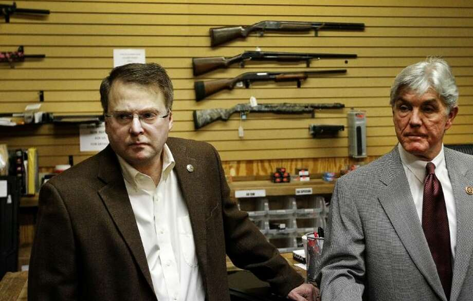 Sen. Brian Birdwell, left, and U.S. Rep. Roger Williams, from Texas's 25th Congressional District, listen to a question from a citizen Friday at the Off Duty Armory, a gun store and shooting range in Burleson. Photo: Ron Jenkins