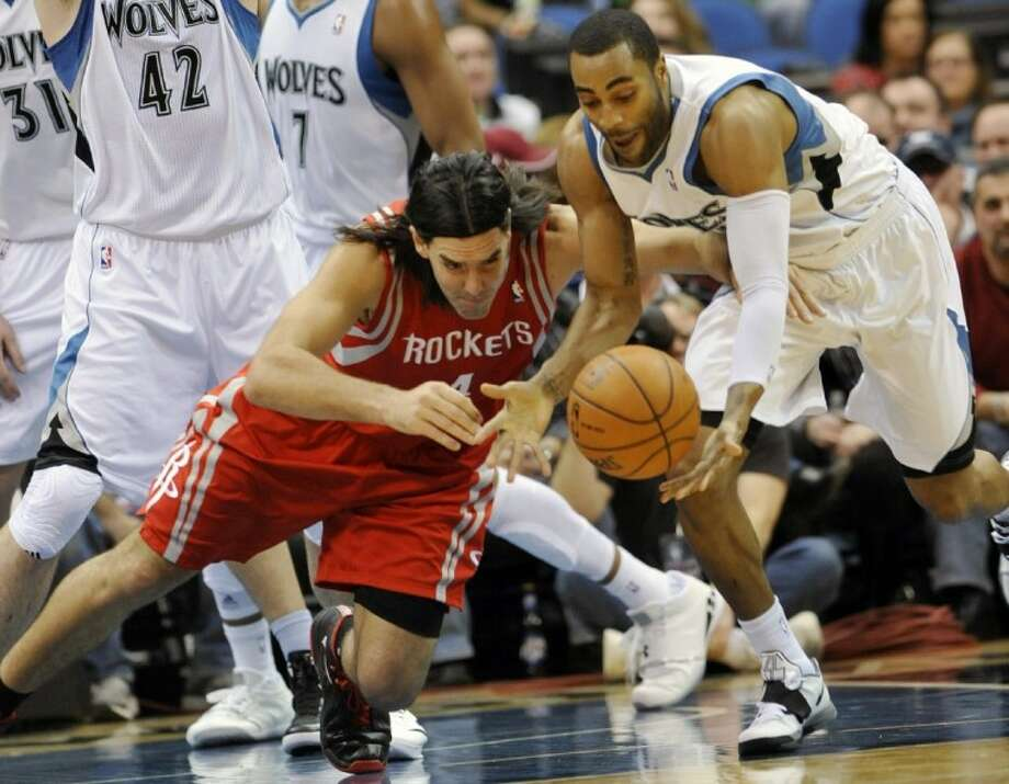Minnesota Timberwolves' Wayne Ellington, right, and Houston Rockets' Luis Scola go after a loose ball in the first half Monday in Minneapolis. Photo: Jim Mone