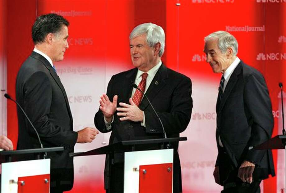 Republican presidential candidate former House Speaker Newt Gingrich, center, talks with former Massachusetts Gov. Mitt Romney, left, and Rep. Ron Paul, R-Texas, right, during a break in a Republican presidential debate Monday, Jan. 23, 2012, at the University of South Florida in Tampa, Fla. (AP Photo/Paul Sancya) Photo: Photo By Paul Sancya / AP