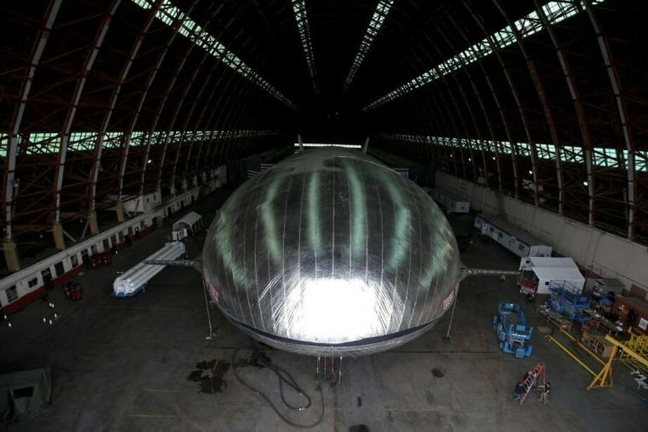 The Aeroscraft airship, a high-tech prototype airship, is seen in a World War II-era hangar in Tustin, Calif., Thursday, Jan. 24, 2013. Work is almost done on a 230-foot rigid airship inside a blimp hangar at a former military base in Orange Co. The huge cargo-carrying airship has shiny aluminum skin and a rigid, 230-foot aluminum and carbon fiber skeleton. Photo: Jae C. Hong