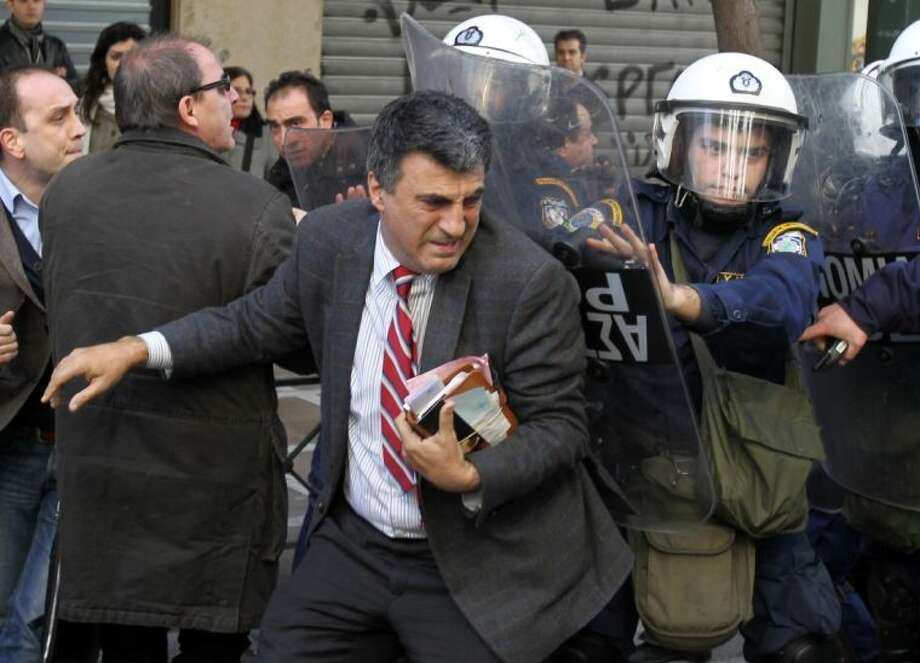 Riot police use shields to move away supporters of detained protesters from outside the Labor Ministry in Athens, Wednesday, Jan. 30, 2013. Protesters from a Communist-backed labor union forced their way into a government building and clashed with police who used tear gas to expel them. Members of the union are protesting planned reforms to the country's pension and income contribution system — part of ongoing austerity cuts demanded by Greece's euro partners and the International Monetary Fund who are keeping the country afloat with emergency loans. Photo: Thanassis Stavrakis